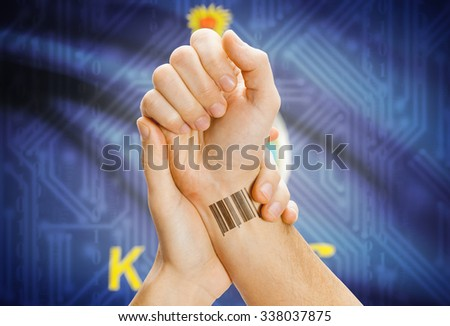 Barcode ID number tattoo on wrist and USA states flag on background - Kansas - stock photo