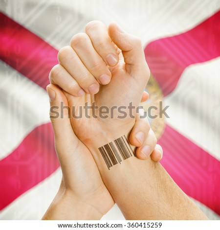 Barcode ID number tattoo on wrist and USA states flag on background series - Florida