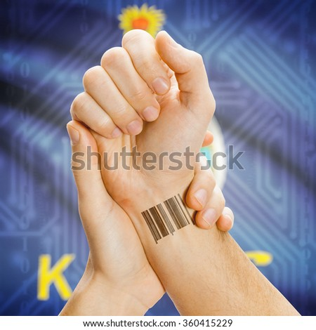 Barcode ID number tattoo on wrist and USA states flag on background series - Kansas - stock photo