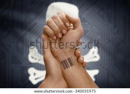 Barcode ID number tattoo on wrist of dark skinned person and flag on background - Jolly Roger flag - symbol of piracy - stock photo