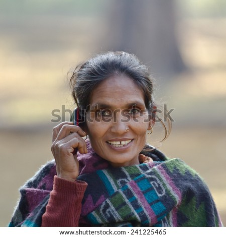 Bardia, Nepal - January 15, 2014: Taru ethnic woman talking with mobil phone in Nepal - stock photo