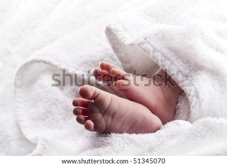 Bare baby feet wrapped in a white towel - stock photo