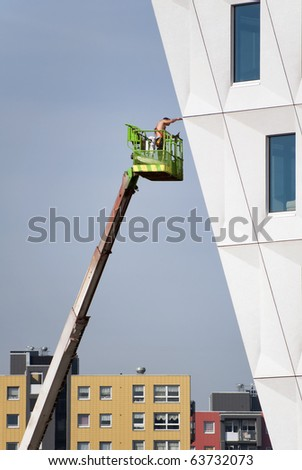 Bare chested construction worker wearing safety harness on an aerial access platform - stock photo