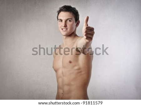 Bare-chested handsome young man with thumbs up - stock photo