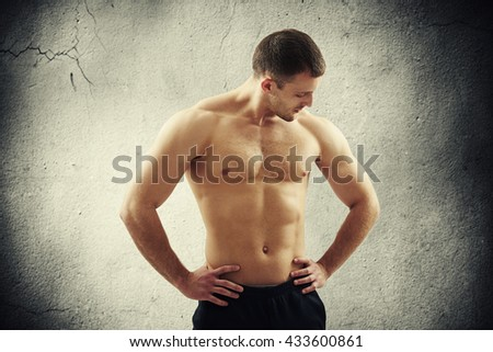 Bare-chested healthy handsome muscular man in black pants is standing over concrete wall and looking down with his hands on hips