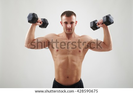Bare-chested young athletic man in black pants is standing isolated over white background and holding up dumbbells - stock photo