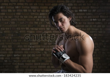 Bare chested young Malaysian boxer wearing fingerless boxing gloves - stock photo