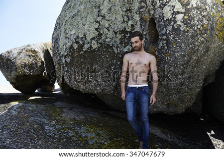 Bare chested young man standing on rocks - stock photo