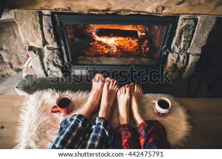 Bare couple feet by the cozy fireplace. Man and Woman relaxes by warm fire with a cup of hot drink and warming up her feet. Close up on feet. Winter and Christmas holidays concept - stock photo