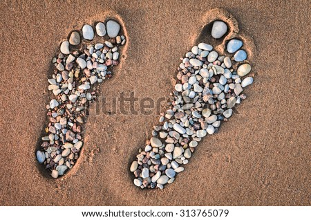 Bare feet made of pebble on the sandy beach - stock photo