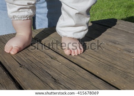 Bare feet of a baby doing his first steps over weathered wooden background. Natural light