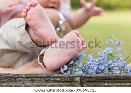 Bare feet of a cute baby on the wooden background. Forget me not and a child. Childhood in the farm. Retro style image of infant and flowers.Small bare feet of a little baby girl. - stock photo