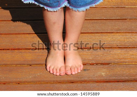 Bare feet of child on wooden deck in sunshine outdoors - stock photo