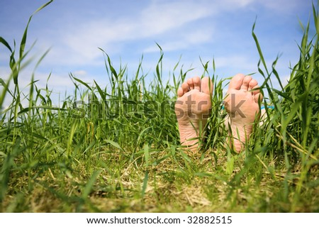 Bare feet of the person having a rest in a grass - stock photo