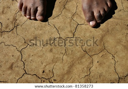 Bare feet on drought stricken earth - stock photo