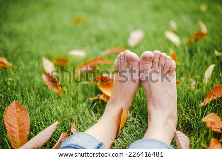 bare feet on green grass with autumn leaves, copy space - stock photo