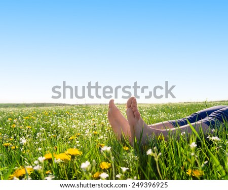 bare feet on spring grass and flowers - stock photo