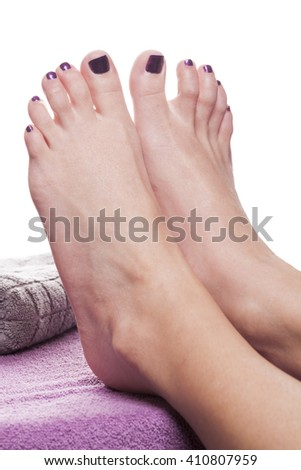 Bare feet with pedicure propped by towel on soft purple treatment table against white background - stock photo