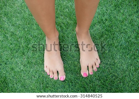 Bare feet woman stepping on the grass  - stock photo
