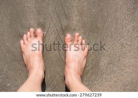 Bare female feet on the shore washed by the sea