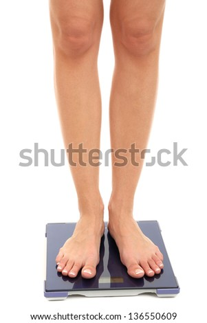 Bare female feet standing on scale isolated on white