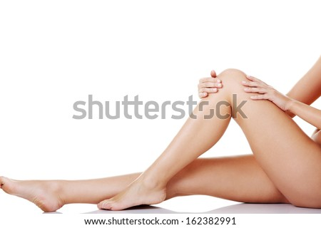 Bare female's legs. Horizontal view. Isolated on white.