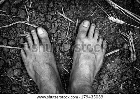 Bare foots over dry soil - stock photo