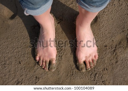 Bare human feet in the sludge - stock photo