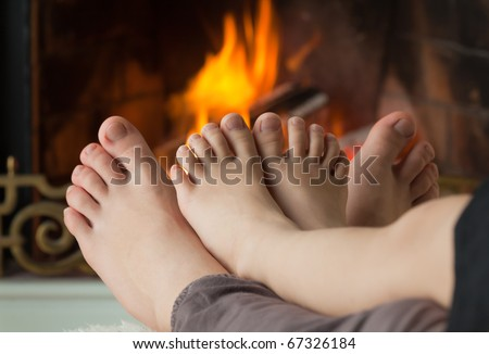 Bare legs a little girl and her sisters are heated by an open fire hearth - stock photo
