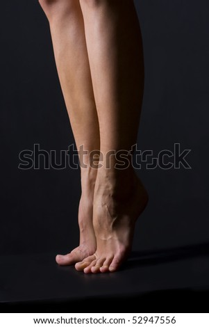 Bare legs on a black background - stock photo