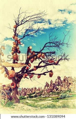 Bare tree with crocks on the branches in beautiful Cappadocia mountains. Retro style photo.