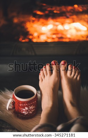 Bare woman feet by the cozy fireplace. Woman relaxes by warm fire with a cup of hot drink and warming up her feet. Close up on feet. Winter and Christmas holidays concept. - stock photo