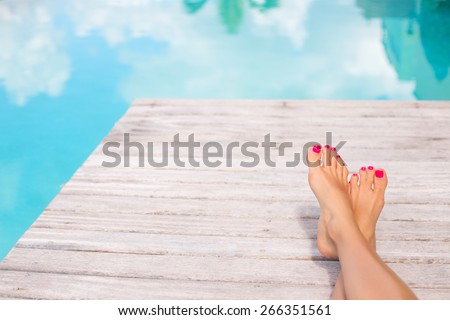 Bare woman feet by the swimming pool - stock photo