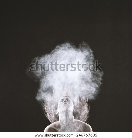Bare Young Woman Throwing Head Back, with Hair Flying Up, Styled with Smoke Effect. Captured on Gray Background
