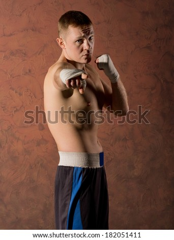 Barechested handsome young boxer with a determined expression pointing at the camera with his bandaged hand - stock photo