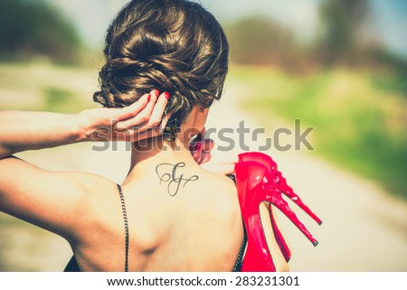 Barefoot brunette girl outdoor with red high heels in her hands - stock photo