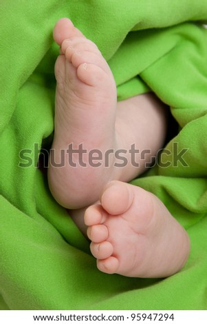 Barefoot child covered by a blanket - stock photo