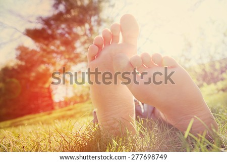 Barefoot child lying on green grass outdoors.  Instagram effect - stock photo