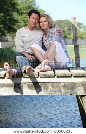 Barefoot couple by the water - stock photo