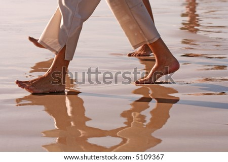 Barefoot couple (feet and legs only) walking on sandy, wet beach - stock photo