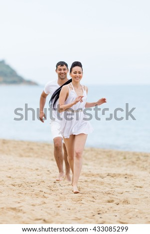 Barefoot couple on sand seashore in cloudy day. Young man in white shorts and T-shirt catches young woman in white sundress on sand beach - stock photo
