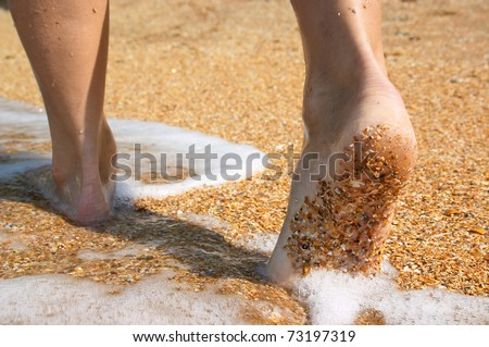 Barefoot feet walking in surf on sand coast