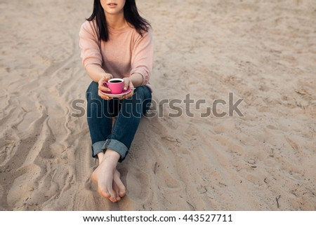 barefoot female on the beach and with cup of coffee; bootless woman sitting on sand in rays of sunset and drinking hot tea;