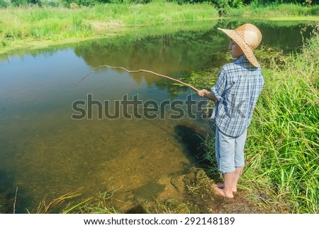 Barefoot fishing boy is standing and angling in transparent brownish waterbody - stock photo