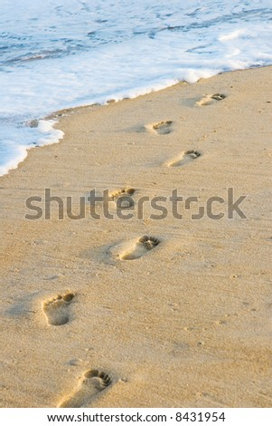 Barefoot footprints on the beach with a wave coming in