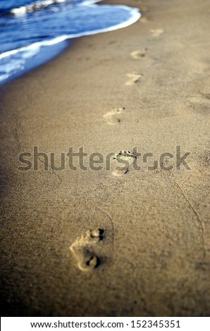 Barefoot footsteps in a sand with sea waves in background. - stock photo