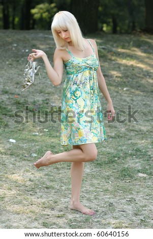 barefoot girl in a sarafan with sandals in hand - stock photo