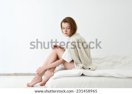 Barefoot girl in a white room sitting on the bed - stock photo
