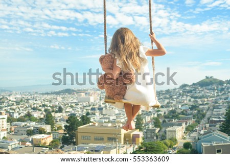 Barefoot girl in white dress hugging teddy bear, flying on vintage swings high above city, view from behind