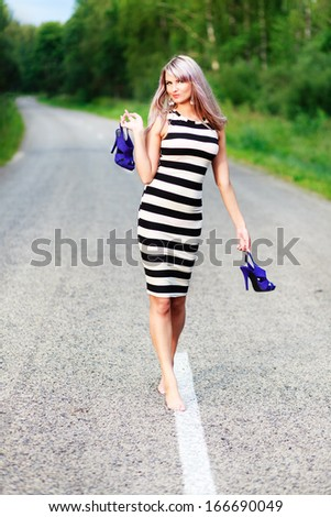 Barefoot girl walking along the road with shoes in a hand. - stock photo